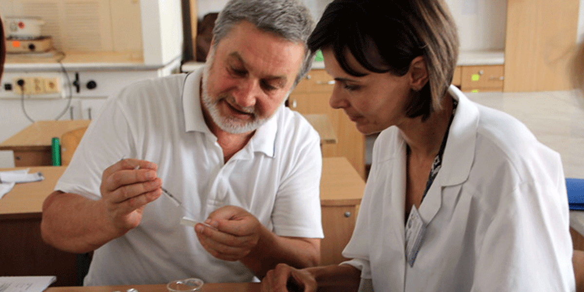 Professor Volodymyr Lushchak, head of the department, demonstrates usage of a microliter syringe to Kateryna Ruzhelnyk