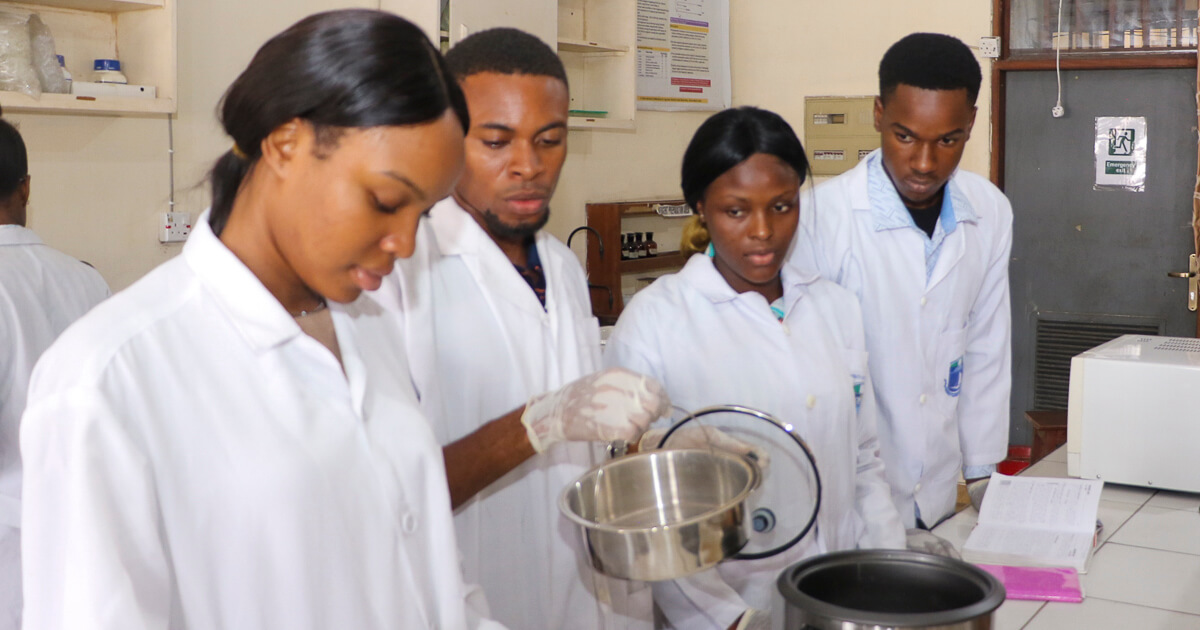 Plant Science and Biotechnology students screening cowpea grains for short cooking time with hand-held pH meter and pressure cooker