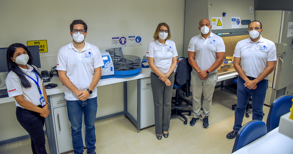 UNIBE researchers in the Institute of Tropical Medicine and Global Health, standing around the newly-installed automated RNA extractor which will significantly expand and accelerate COVID-19 diagnostic testing in the Dominican Republic